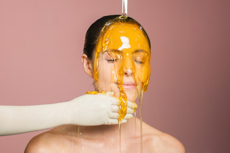 honey mask poured on woman's face