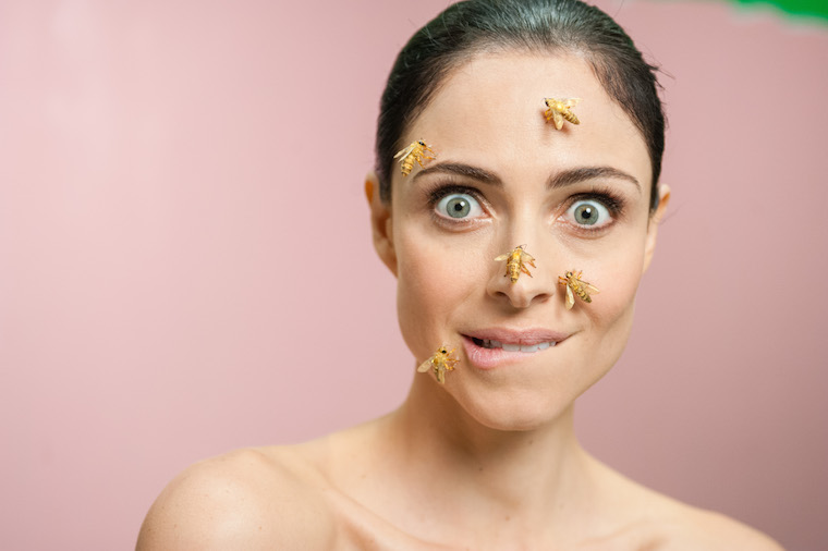 woman looking surprised with bees on her face