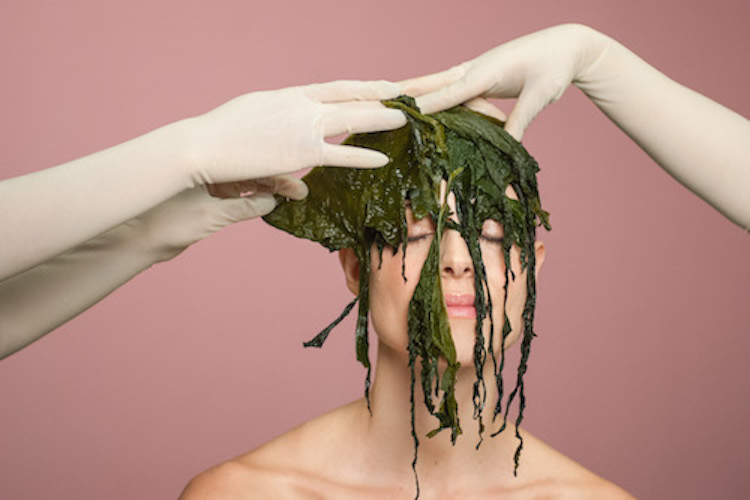 two hands placing seaweed on woman's face
